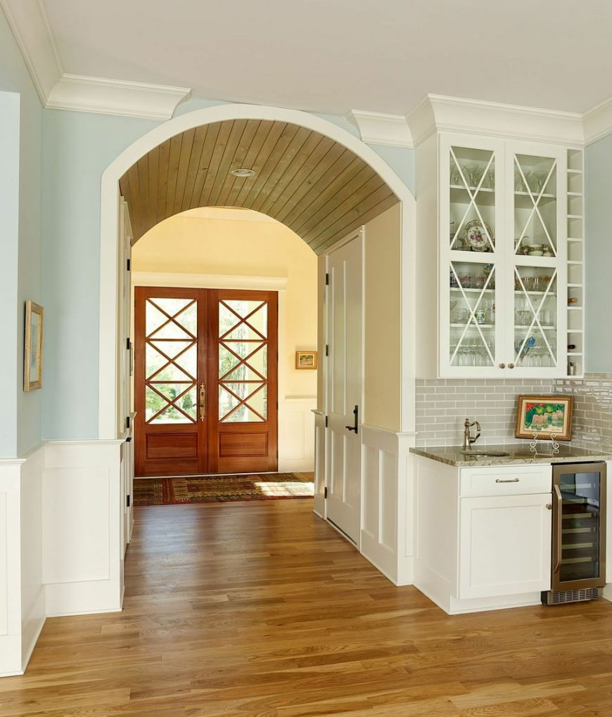 This farmhouse foyer features a vinyl flooring together with white and bright blue walls. There's an archway ceiling in the hallway adding elegance to the home.
