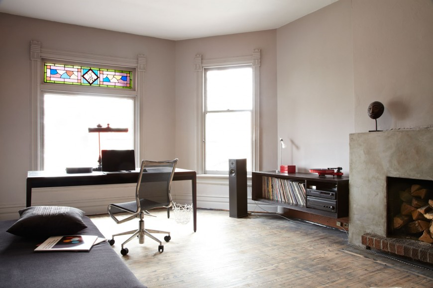 Rustic bedroom features a home office by the window fitted with lovely stained glass. It has a dark wood office desk paired with a mesh office chair.