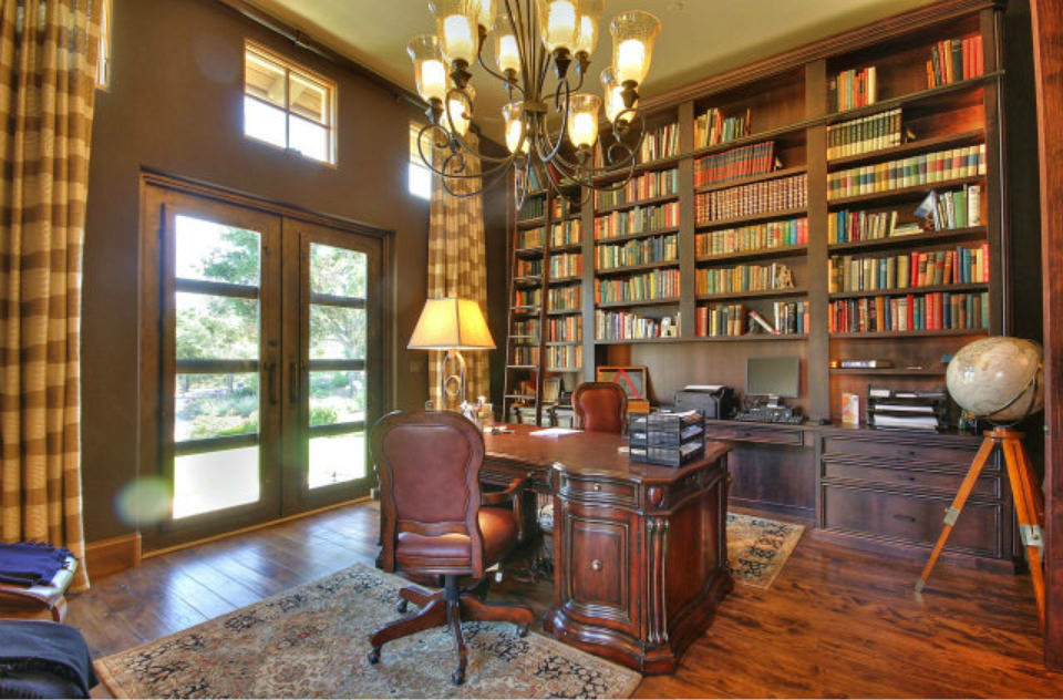 Tuscan home office with a wood plank flooring and a french door covered with striped draperies. It includes a carved wood desk facing the full height bookshelf that's illuminated by a wrought iron chandelier.