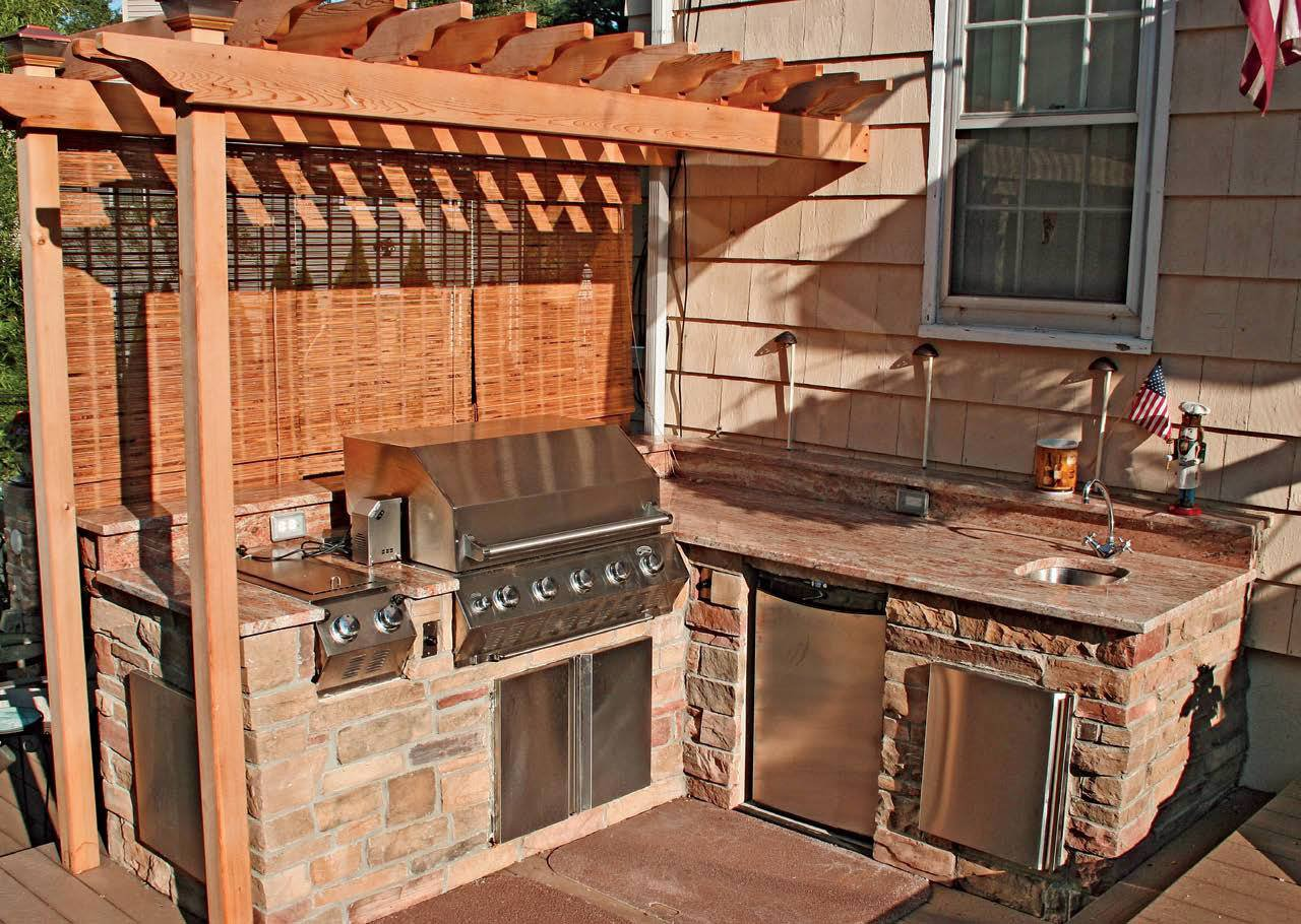 This outdoor kitchen boasts a medium bar built in stone bricks and has a smooth countertop.