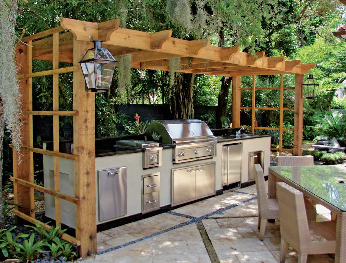 This outdoor kitchen features a modish bar setup with stainless steel appliances and black countertop near the dining table set.