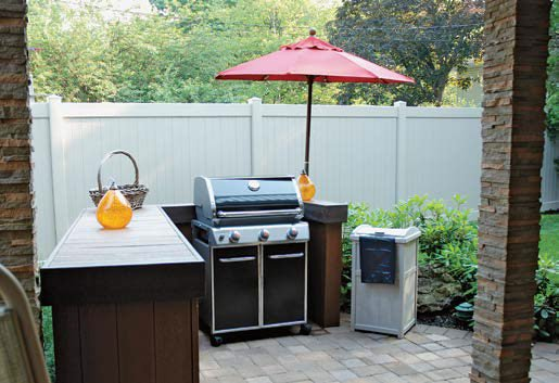 An outdoor kitchen featuring a small bar with a modern grill and stove.