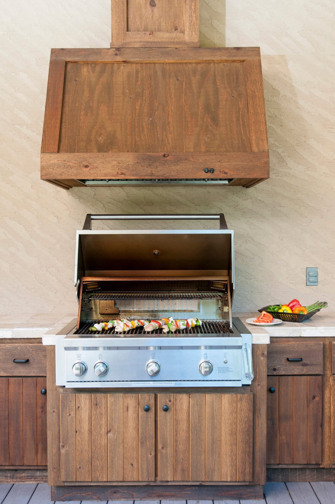 This outdoor kitchen on the home's deck features a bar built in wooden and a smooth marble countertops.