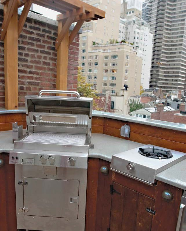 A close up look at the outdoor kitchen's bar counter and stainless steel appliances.