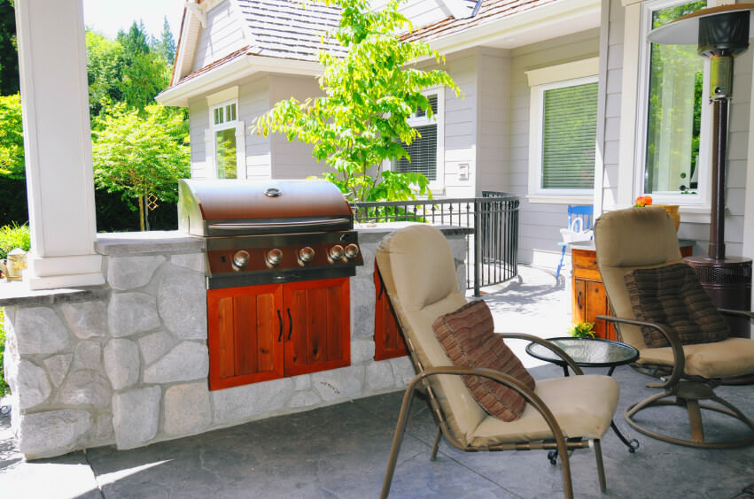 This outdoor kitchen boasts a medium-built bar and counter set with a classy outdoor living set.
