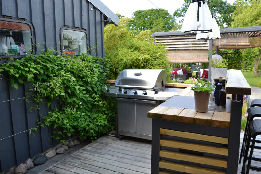 This outdoor kitchen set on the home's deck boasts a stylish bar and counter set with wooden countertops.