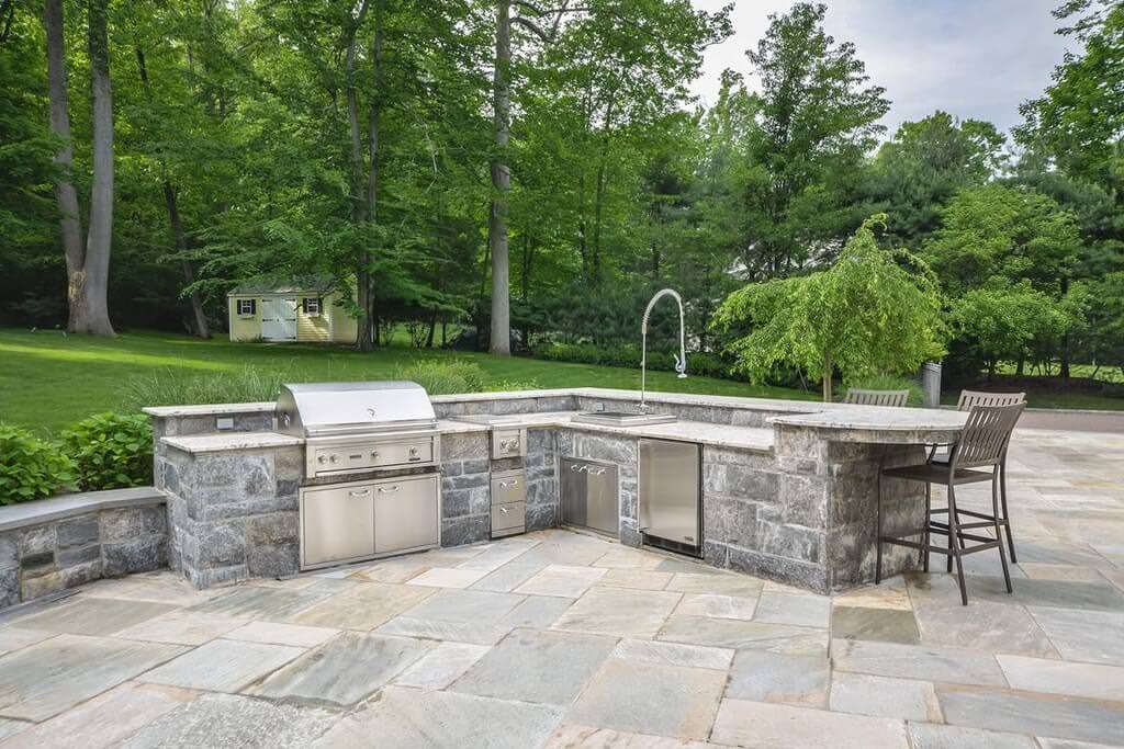 Outdoor kitchen featuring a stone-made L-shape bar counter with marble countertop and a space for a breakfast or drinking bar.