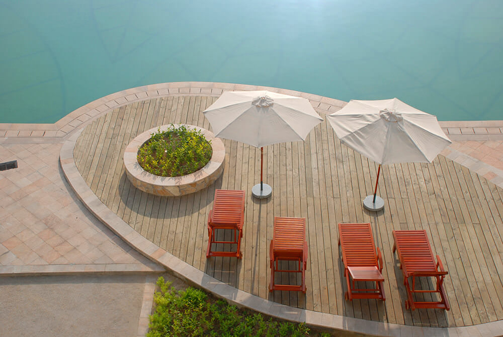 This deck features a set of lounger seats with a couple of umbrellas giving shade overlooking the stunning pool area.