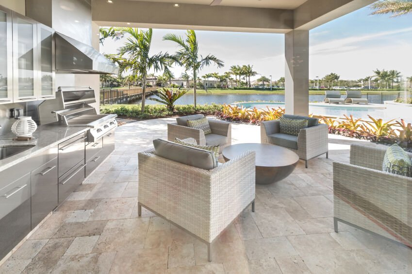 Large outdoor kitchen boasting a modish bar and counter set along with an outdoor living set.