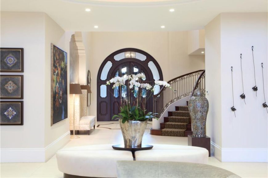 A glamorous home entry with white walls and multiple artistic wall decors, as well as a curved staircase with carpet floors.