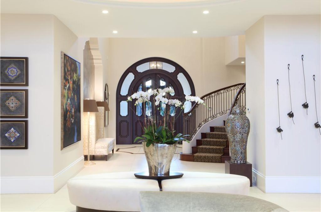 Elegant foyer featuring white tiles flooring and walls decorated by elegant framed pictures and arts.