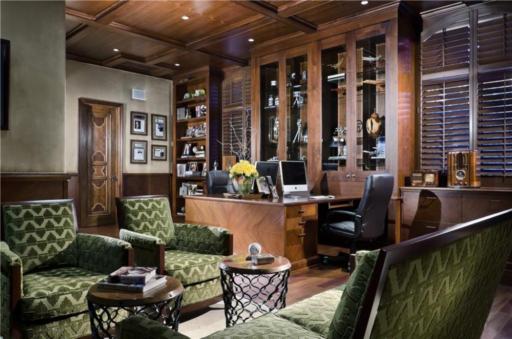 Large home office with a luxurious desk and shelves that match perfectly with the coffered ceiling. The green chairs add class to the room.