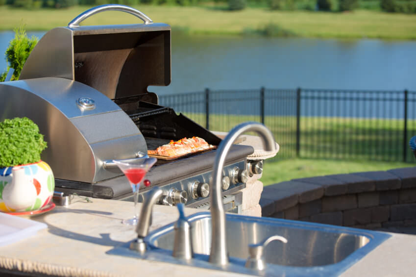 A close up look at this outdoor kitchen's counter and grill stove.