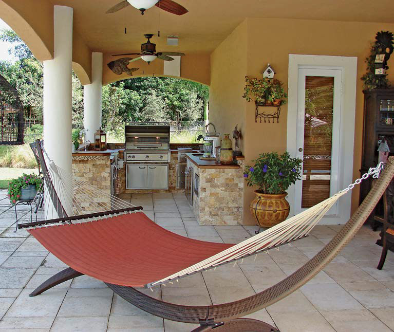 Outdoor kitchen featuring a large bar made of stone bricks lighted by ceiling fan lighting. There's a hammock swing nearby the kitchen area.