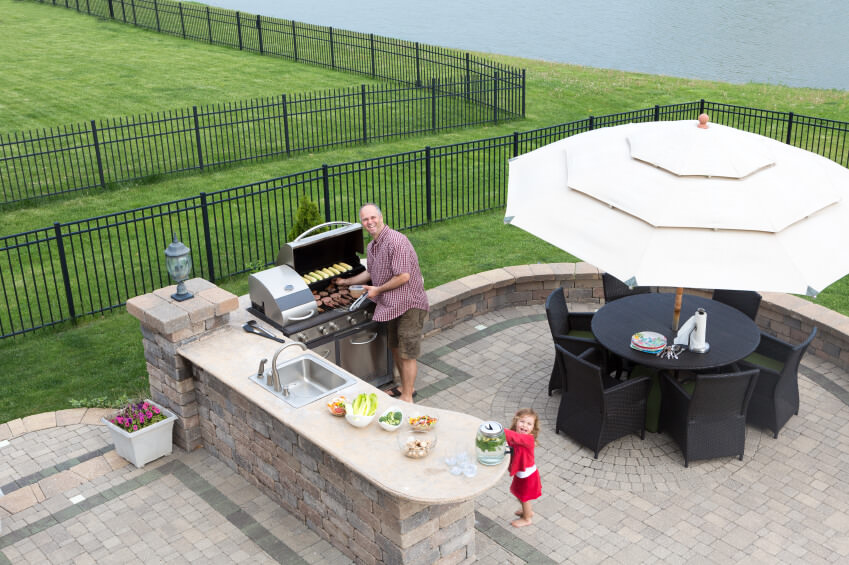 This outdoor kitchen boasts a smooth counter and a stylish black round table set.