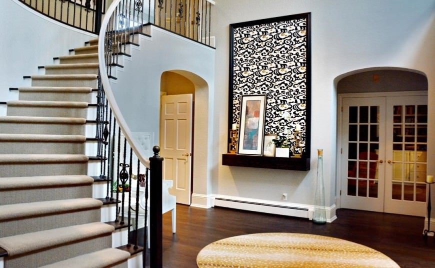 This entryway is decorated with a lovely black framed artwork along with a curved staircase fitted with ornate wrought iron spindles and wooden treads covered with a beige carpet.