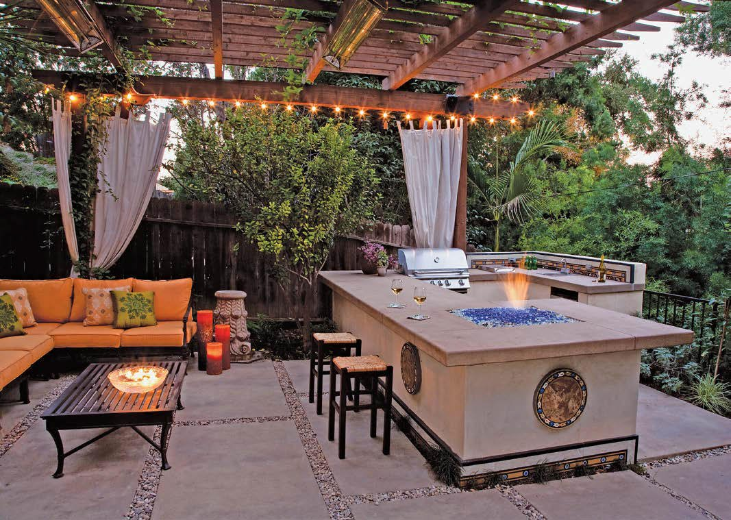 Glamorous outdoor kitchen featuring a large bar with a custom fire pit and a patio-type sofa set.