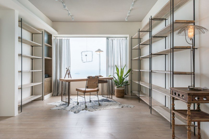 Fresh home office showcases a natural wooden desk and chair that sit on a cowhide rug on a slanted layout. It is lighted by parallel track lights and natural light from the glazed window.