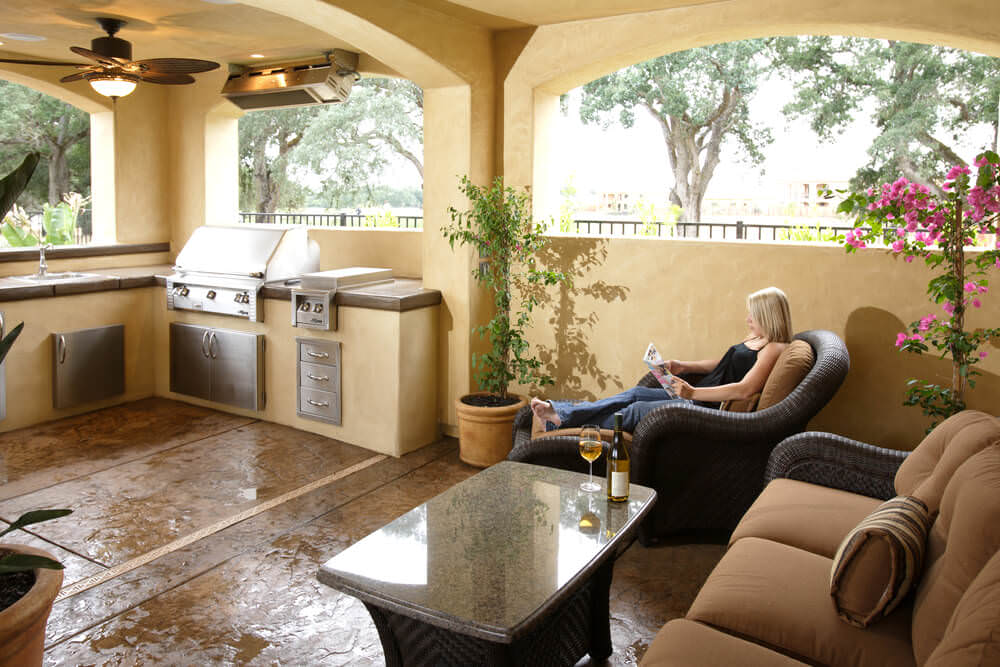 This outdoor kitchen boasts an L-shaped bar with smooth countertops along with an outdoor living set on the side.