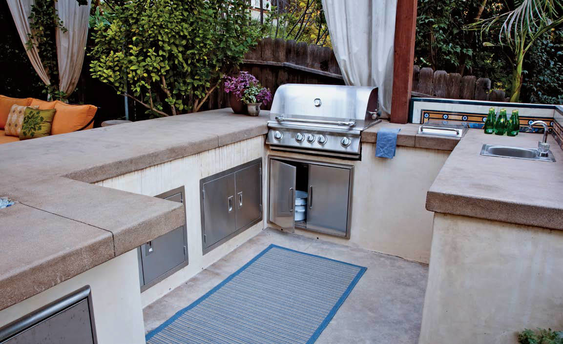 Outdoor kitchen with a large bar setup with smooth countertop and stainless steel appliances.