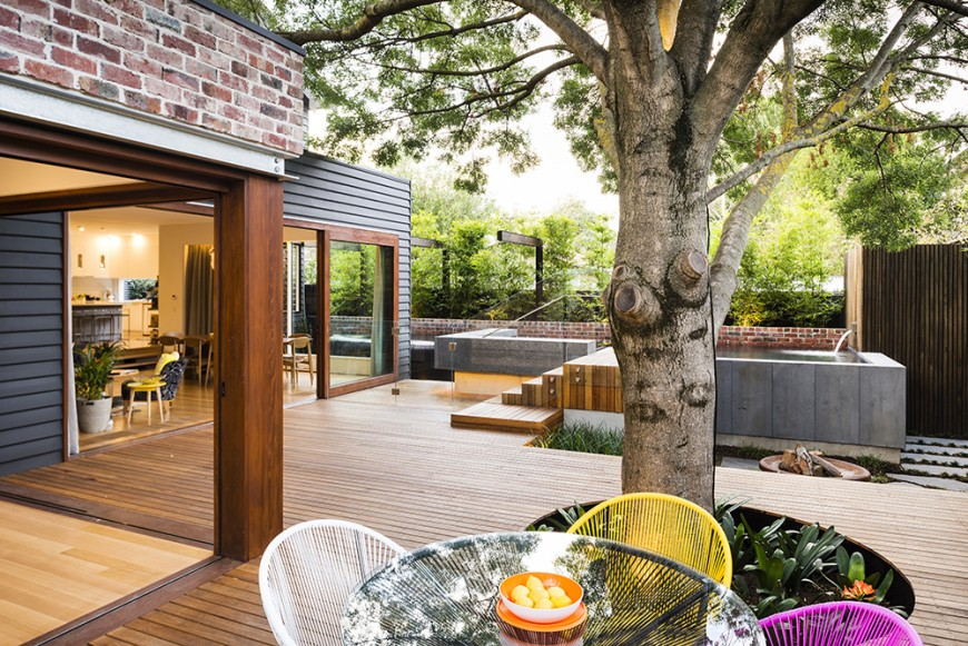 This deck offers a cozy pool and jacuzzi along with a small dining table set near the matured tree providing shade.