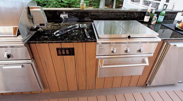 Close up look at this outdoor kitchen's bar with a smooth black countertop perfect with the stainless steel appliances.