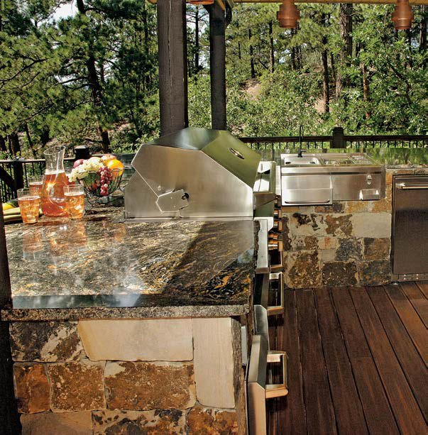 An outdoor kitchen set on the home's deck featuring a stylish bar made of stone bricks with a stylish countertop.