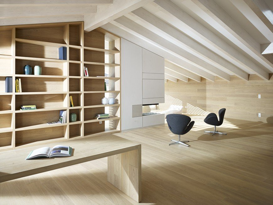 Spacious home office with white wood beam cathedral ceiling that blends well with the light wood plank flooring and wall. It includes a pair of modern black chairs along with a wooden bench facing the full height open shelves.
