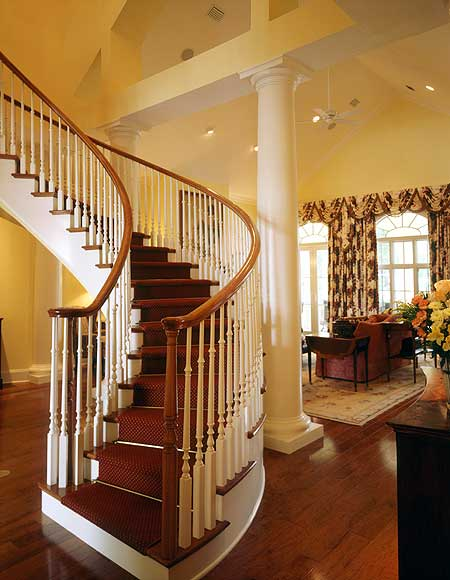 A curved staircase with elegant red carpet floors and white railings.