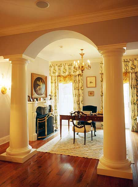 A classy home office lighted by a fancy brass chandelier and framed with huge columns forming an open archway. It has rich wood plank flooring and glass windows dressed in charming draperies with valences.