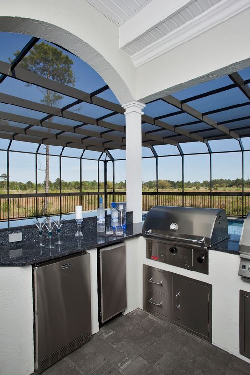 This outdoor kitchen features a stylish bar counter set equipped with black granite countertop.