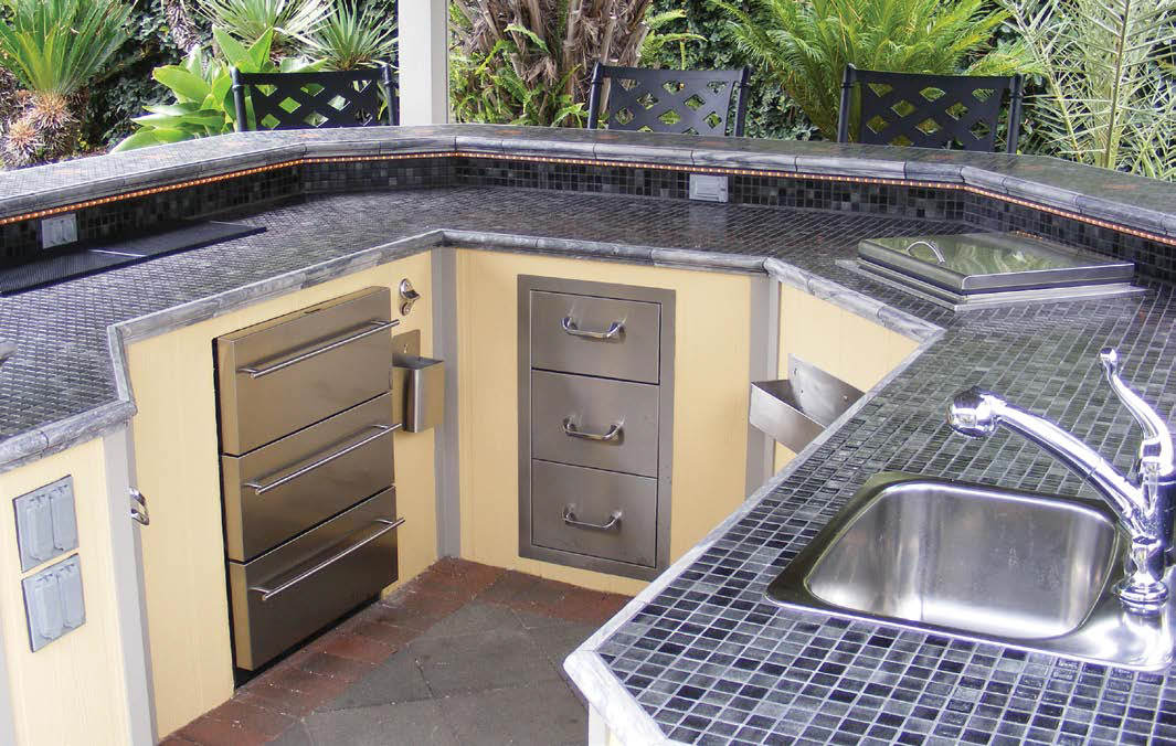 This outdoor kitchen offers a modish bar setup with black and gray tiles countertop and breakfast bar.