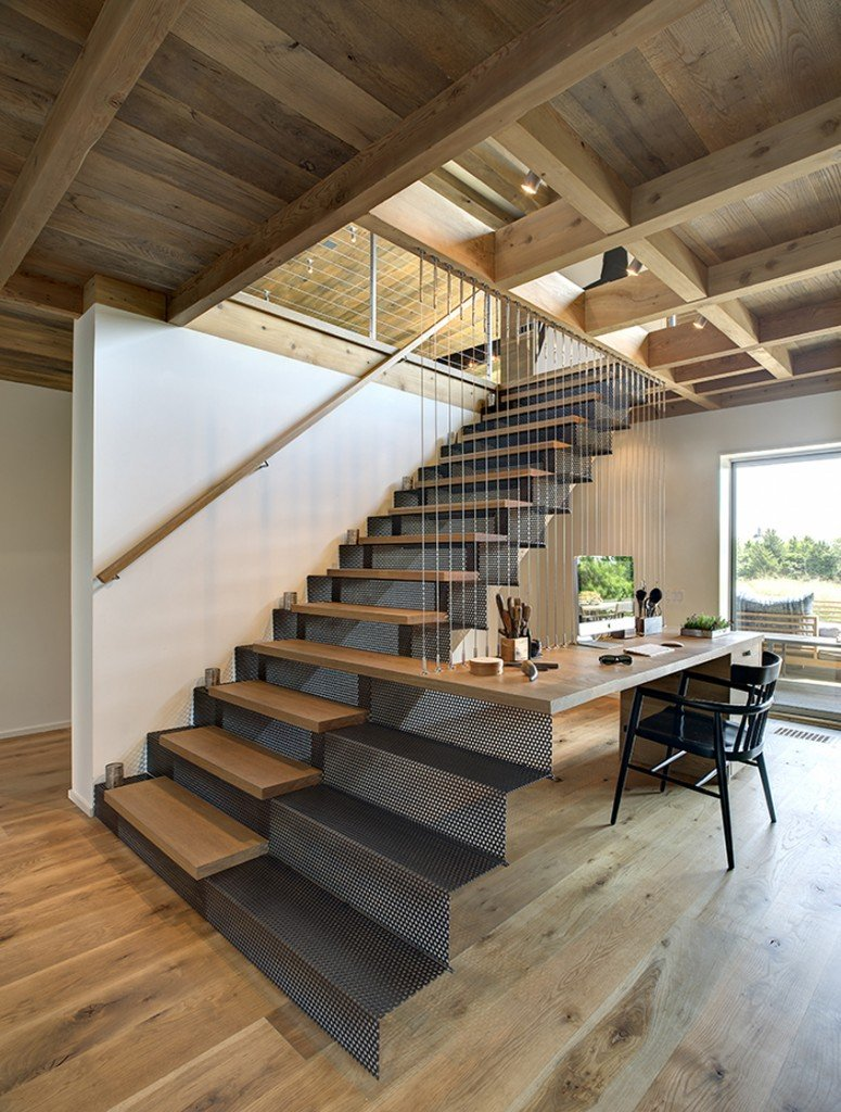 The cozy home office showcases a perforated staircase that extends to the office desk framed with thin metal rods.