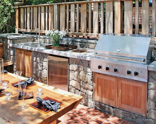 This outdoor kitchen boasts a stone-made bar with a smooth countertop and a wooden dining table set.