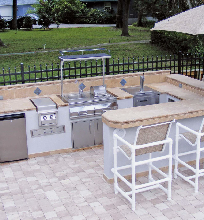 This outdoor kitchen offers a large bar with marble countertop. The appliances look perfectly well.