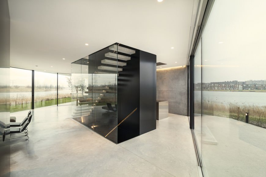 Spacious foyer surrounded with floor to ceiling windows overlooking a stunning outdoor scenery. There's a black staircase in the middle lined with glass panels.