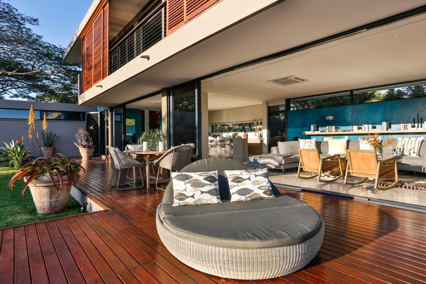 Wide and modern deck offering a large and soft lounging spot for two along with a small dining table set.