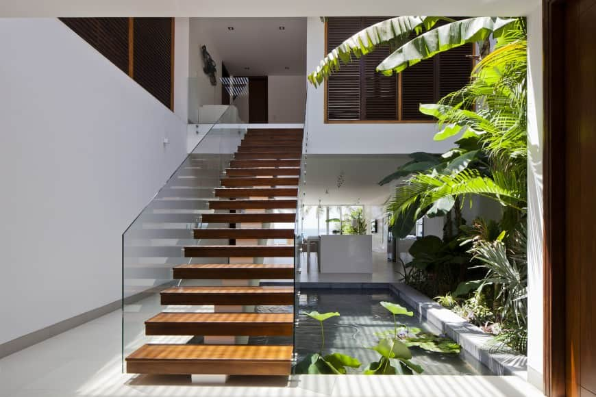 Fresh foyer showcasing indoor plants and a water feature underneath a single stringer staircase with open risers and wood treads framed with glass railings.