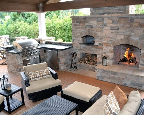 Outdoor kitchen with a small bar counter and a patio area near the fireplace.
