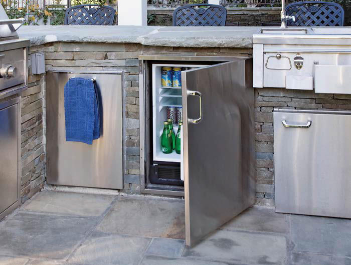 Small outdoor kitchen set on a tiles flooring. The counter is made of bricks and concrete countertop.