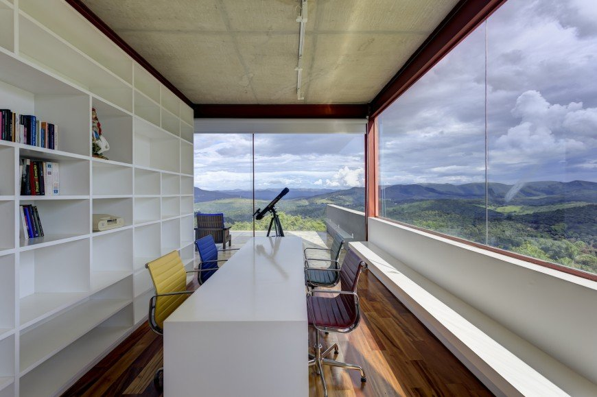 Glazed home office with rich hardwood flooring and panoramic windows overlooking an impressive mountain view. It has a sleek white table surrounded by multi-colored office chairs.