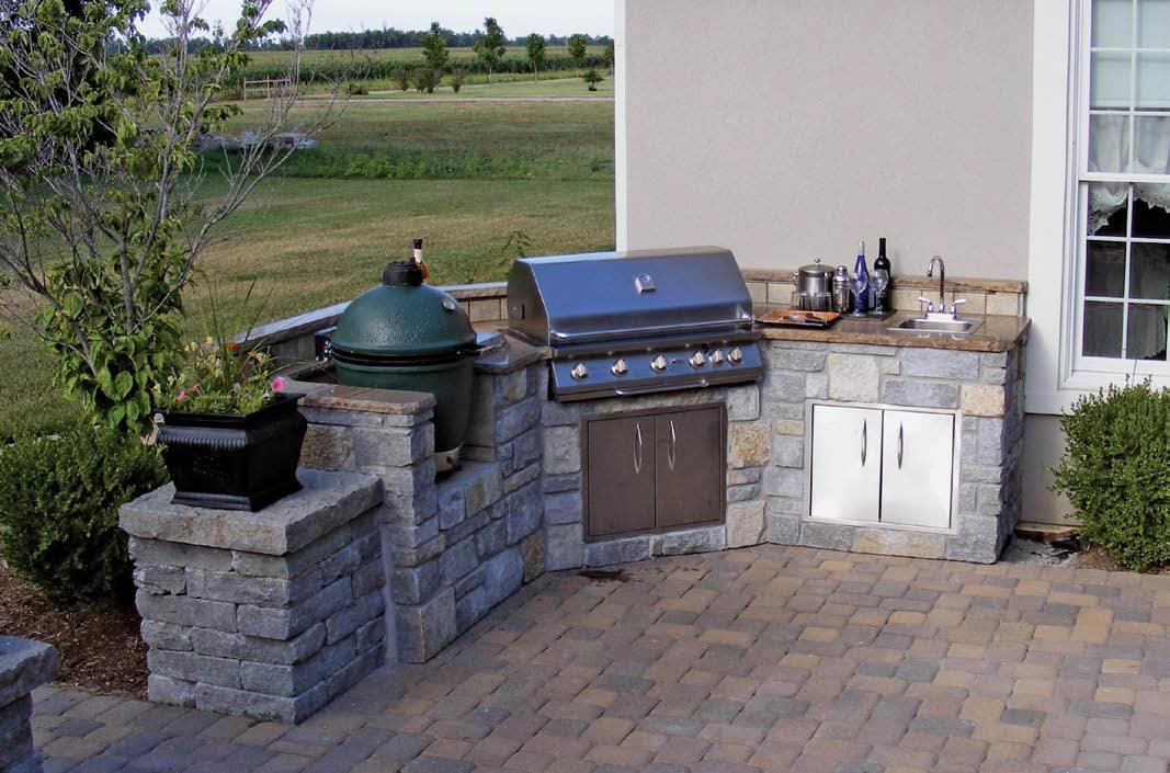 This outdoor kitchen set on brick tiles flooring features a small bar made of bricks with a granite countertop.
