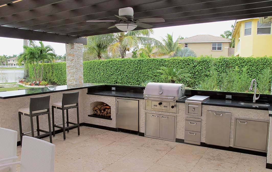 Large outdoor kitchen featuring a long and modish counter with a granite countertop.