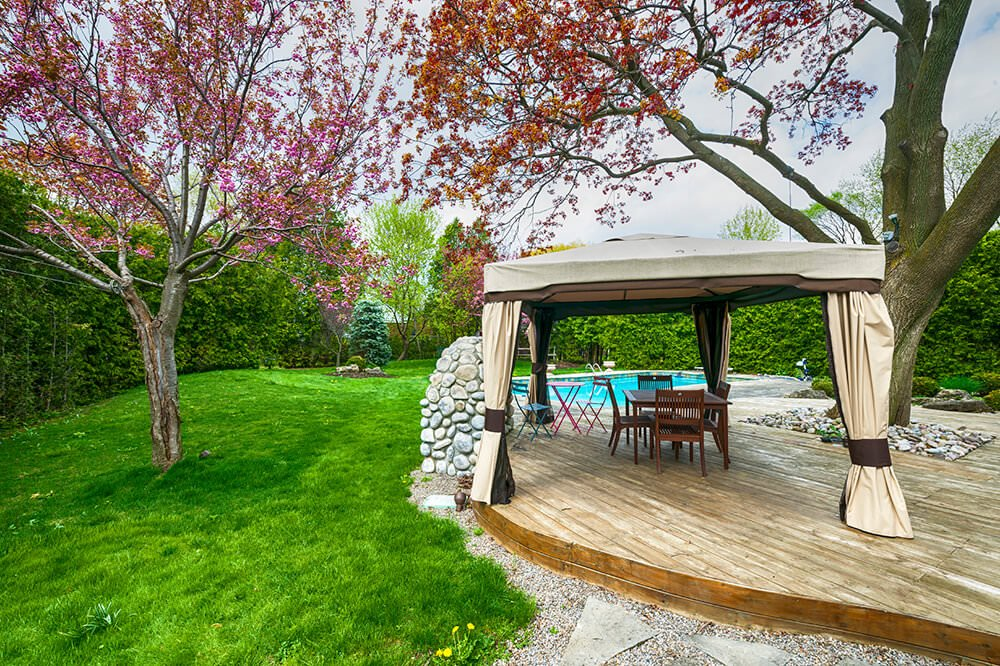 This wide and long features a shaded small dining table set near the trees with blooming pink flowers.