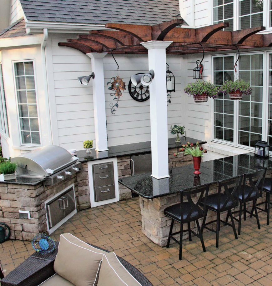 An outdoor kitchen set on a brick tiles flooring featuring a breakfast bar with a granite countertop along with a set of bar stools.