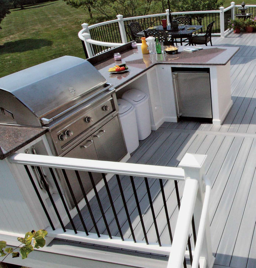 This outdoor kitchen has a modish bar set on the home's deck. The countertop looks gorgeous. There's a set of stainless steel appliance as well.