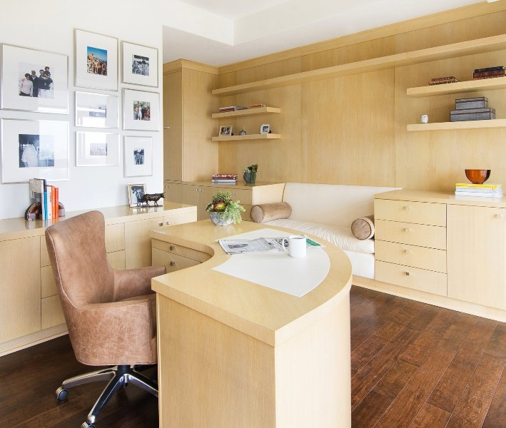 Charming home office features white gallery frames mounted above the light wood cabinet that matches with the curved office desk and built-in storage fitted with a white seating in the middle.