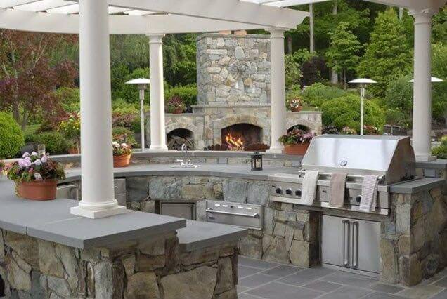 Large U-shape outdoor kitchen with stone-made bar counters and thick concrete countertops.