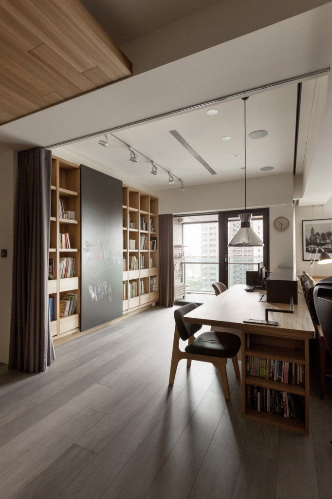 A chrome pendant illuminates this home office along with recessed and track lights fixed on the white ceiling. It has a natural wood desk fitted with built-in shelves.