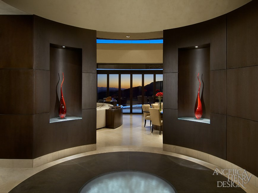 This luxurious foyer showcases a round flooring accented with fiber optic lighting. It is designed with lovely red decors on a dark brown wall.